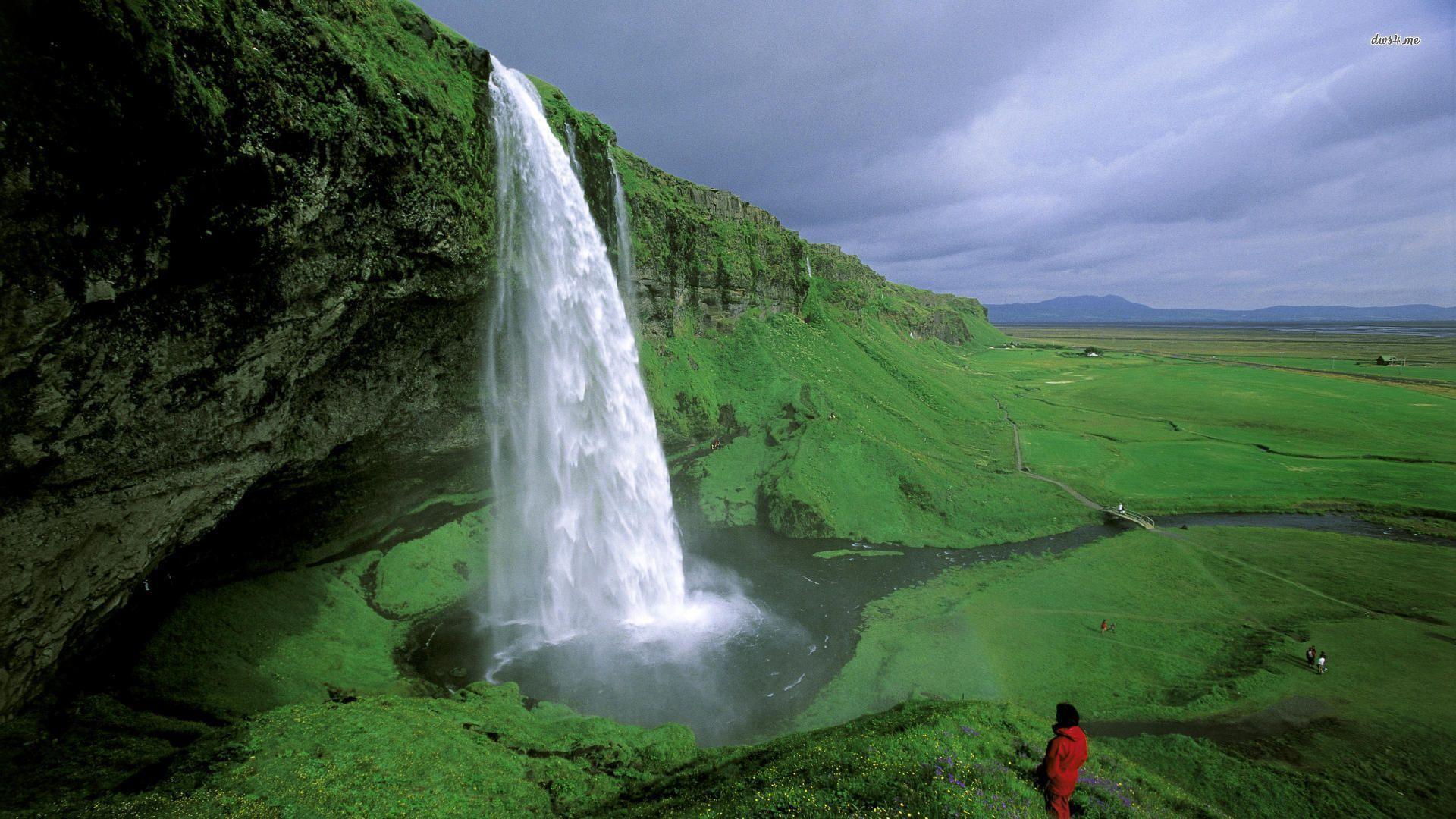 Islande, cascade de Seljalandafoss, verdure, personnes de dos au premier plan